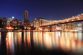 Queensboro Bridge over New York City East River at sunset with river reflections and midtown Manhatt