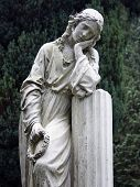 stock photo of grieving  - Stone statue of a grieving young woman - JPG