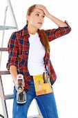 Worried DIY handy woman standing with her hand to her forehead and a wide eyed expression holding an