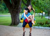 pic of babysitting  - Big sister holding disabled brother on special needs swing at playground in park - JPG