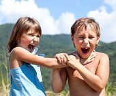 stock photo of strangled  - Angry boy and a girl scream and fight with each other outdoors - JPG
