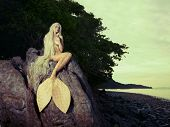 stock photo of mermaid  - Beautiful fashionable mermaid sitting on a rock by the sea - JPG