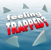Feeling Trapped words on an ocean surrounded by shark fins to illustrate hopelessness, futility and