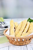 Bread sticks  in wicker basket on wooden table on light background