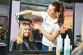 picture of beauty parlour  - Female hairdresser drying hair with blow dryer of woman client at beauty parlour after highlighting - JPG