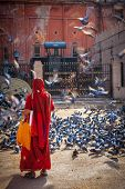 JAIPUR, INDIA - NOVEMBER 18, 2012: Indian woman in sari feeding pigeons in street. Hindus and Sikhs