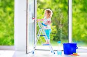 image of girl next door  - Cute laughing curly toddler girl washing a big window with a squeegee in beautiful white living room with door into the garden standing on a ladder next to a blue bucket with water detergent solution spray bottle and sponge - JPG