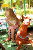 image of merry-go-round  - Happy beautiful girl on a colorful merry - JPG
