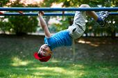 image of upside  - Little boy in red cap upside down at playground outdoor activity dangerous - JPG