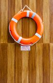 Picture of the orange life buoy hanging on the wood wall for safety and rescue.