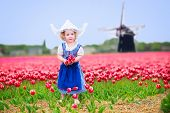 pic of national costume  - Adorable curly toddler girl wearing Dutch traditional national costume dress and hat playing in a field of blooming tulips next to a windmill in Amsterdam region Holland Netherlands - JPG