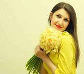 image of jonquils  - Young happy woman with a big bouquet of flowers in her hands - JPG