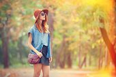foto of redhead  - Redhead girl in sunglasses and hat in the autumn park - JPG