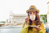 stock photo of piazza  - Young woman drinking coffee on piazza venezia in rome italy - JPG