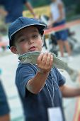 stock photo of trout fishing  - happy child with a trout in his hand while fishing competition  - JPG