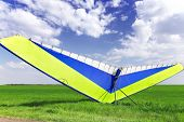 stock photo of glider  - Motorized hang glider over green grass ready to fly - JPG