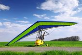 image of glider  - Motorized hang glider over green grass ready to fly - JPG
