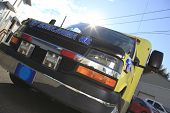 picture of paramedic  - A Paramedic ambulance on the road with sun on the back - JPG