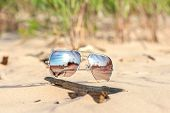 pic of protective eyewear  - Trendy sunglasses with reflection lost on the beach sand - JPG