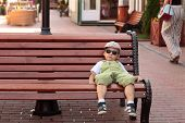 stock photo of bench  - Child resting on a wooden bench in the city - JPG