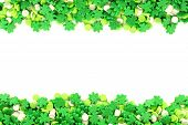 stock photo of sprinkling  - St Patricks Day frame of green shamrock candy sprinkles over white - JPG