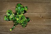 stock photo of saint patrick  - St Patricks Day shamrock made of buttons against an old wood background - JPG