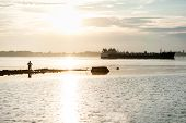 foto of barge  - silhouette of a fisherman and a barge on the river - JPG