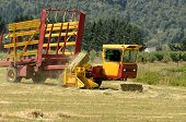 stock photo of hay bale  - Self contaned hay bale wagon picking up bales of alfalfa from a farm field - JPG