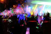 picture of rave  - Color neon streaks of light glow sticks at a night celebration and rave - JPG
