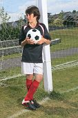 image of 13 year old  - A soccer player holding a ball in a playground - JPG