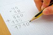 foto of math  - Hand of a child making a multiplication with a pencil - JPG