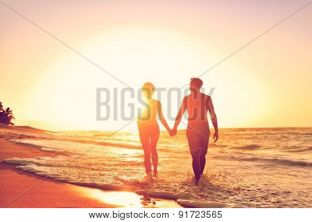 Honeymoon couple romantic in love at beach sunset. Newlywed happy young couple holding hands enjoyin