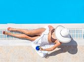 pic of swimming  - Young woman in bikini with a straw hat by the swimming pool - JPG