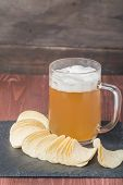 pic of potato chips  - Beer with foam in glass mug and potato chips on wooden table - JPG
