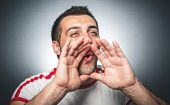 picture of yell  - Closeup portrait mad funny man hands to open mouth yelling over dark gray background studio shot - JPG