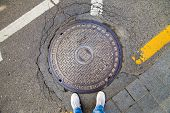 picture of manhole  - Manhole cover in Seoul Korea with man - JPG