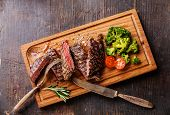 picture of ribeye steak  - Sliced medium rare grilled Beef steak Ribeye with broccoli on cutting board on wooden background - JPG