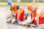 picture of cobblestone  - Two smiling construction workers laying new cobblestones - JPG
