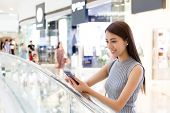 stock photo of department store  - Young lady read the message on cellphone at department store - JPG