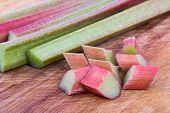 pic of cutting board  - Fresh Rhubarb stalk and pieces on a wooden cutting board - JPG