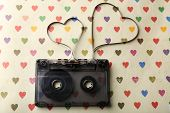 picture of heart sounds  - Audio cassette with magnetic tape in shape of hearts on paper background - JPG