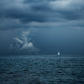 stock photo of sails  - Boat Sailing in Center of Storm Formation - JPG