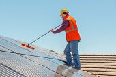 picture of worker  - Young worker cleaning solar panels on the roof - JPG
