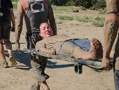 stock photo of stretcher  - Dirty women being carried on stretcher by two men - JPG