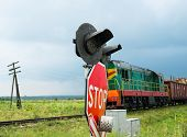 stock photo of railcar  - Traffic lights and signs at the railroad crossing and the approaching freight train  - JPG