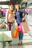 stock photo of mall  - Pretty twins girls having fun with shopping in shopping mall - JPG