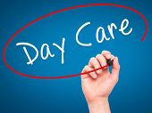 pic of day care center  - Man Hand writing Day Care with marker on transparent wipe board - JPG