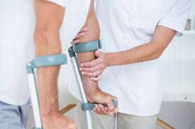 picture of crutch  - Doctor helping her patient walking with crutch in medical office - JPG