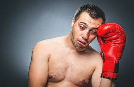 picture of bruises  - Funny close up face of beaten boxer over dark gray background. Kickboxer with bruise on his face - JPG