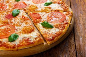 picture of crust  - Delicious italian Margherita pizza decorated with basil leaves  - JPG